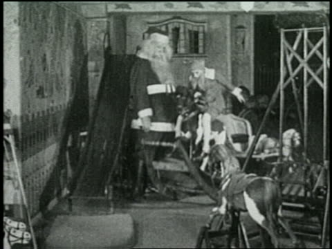 b/w 1925 santa claus watches elf riding rocking horse in workshop - 1925 stock videos & royalty-free footage