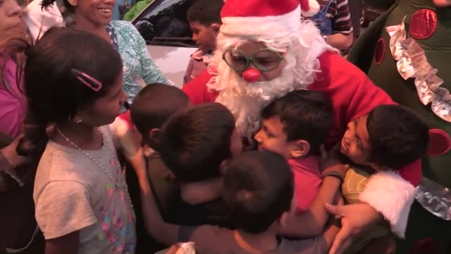 Santa Claus with a red nose and green glasses and accompanied by a group of volunteers scans the streets of crisis hit Caracas Saturday in search of...