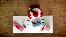 Santa Claus working at office on laptop, smartphone and tablet with chromakey, green screen, typing, aerial view, top down shot