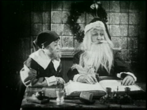 b/w 1925 santa claus working on christmas list with elf - 1925 stock videos & royalty-free footage