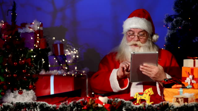 santa claus works on digital tablet - christmas stocking stock videos and b-roll footage