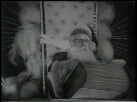vídeos de stock e filmes b-roll de b/w 1951 santa' claus writing in book with quill pen - 1951