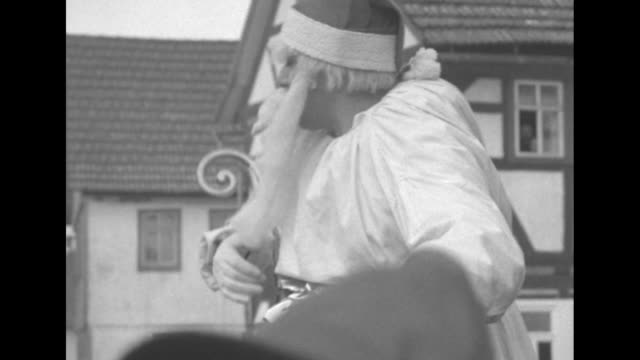 santa, dressed in cap and white robe, cradles staff in arm while he looks through a book and talks / santa hold baby in his arms and lets baby pick... - 羊飼いの棒点の映像素材/bロール