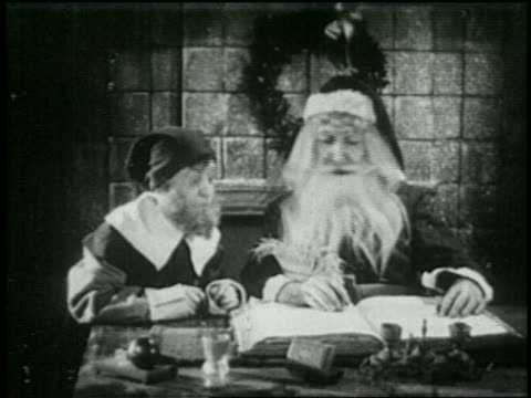 b/w 1925 santa + elf working on christmas list - 1925 stock videos & royalty-free footage