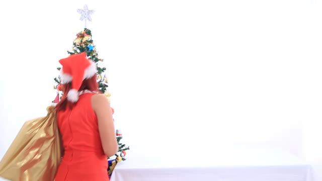 vídeos de stock e filmes b-roll de santa menina colocar um embrulho de presente na mesa - chapéu do pai natal