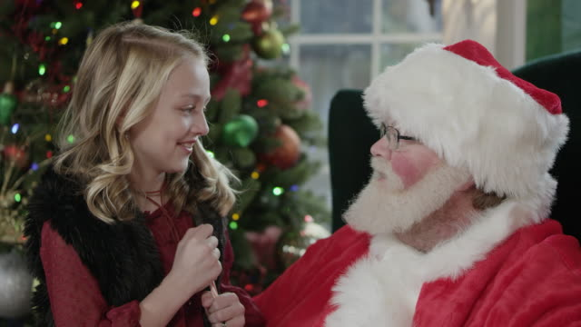 Santa hands girl a candy cane as they talk