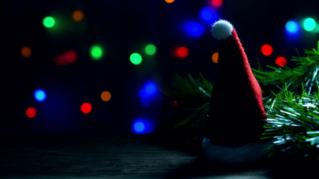 santa hat on old wood, background light of christmas tree, happy new year, copy space, bokeh led light. - santa hat stock videos & royalty-free footage