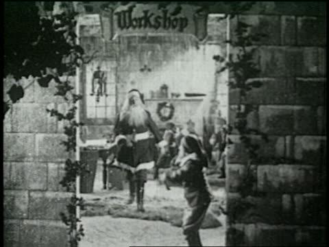 vidéos et rushes de b/w 1925 santa joining elf in doorway of workshop - 1925
