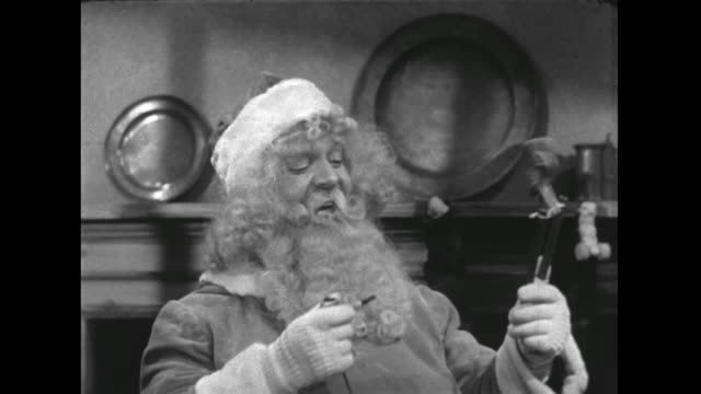1946 Santa laughs and smokes his pipe as he stuffs stockings with toys