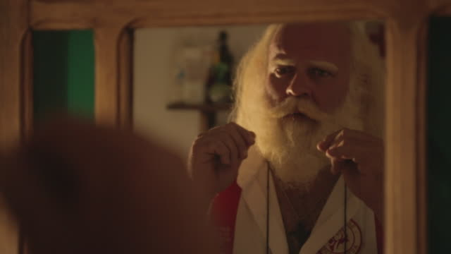 m/s santa looking at a mirror and stroking his moustache and beard - 前ボケ点の映像素材/bロール