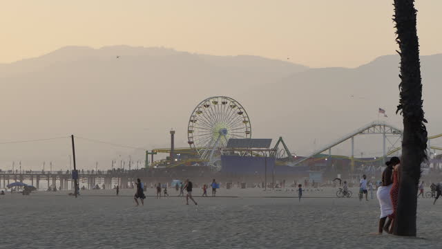 santa monica beach, california, late afternoon camera zooms out from pacific park to people leaving and going to the beach, post sunset. - serene people stock videos & royalty-free footage