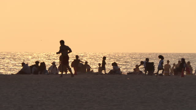 santa monica beach, california, late afternoon people and beach activities, people standing and talking, people laying down on beach towels, ocean... - two parents stock videos & royalty-free footage