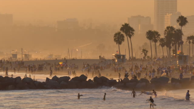 vídeos de stock e filmes b-roll de santa monica beach july 4th holiday idyllic late afternoon beach scene with people enjoying the gentle surf, lifegard stand and palm trees - santa monica
