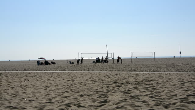 santa monica beach midafternoon people playing volleyball and people sitting on towels watching southern california los angeles - santa monica stock videos & royalty-free footage