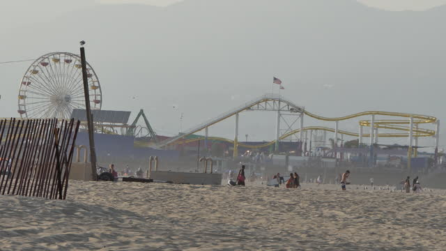 santa monica low angle pov slight tilt up the beach people roller coaster and ferris wheel seen through heat distortion, people are coming and going... - distorted stock videos & royalty-free footage