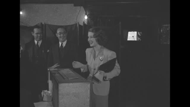 vídeos de stock, filmes e b-roll de ms man giving ballot to election worker / ms norma shearer at voting box election worker puts ballot in box / shearer leaving polling place american... - 1940