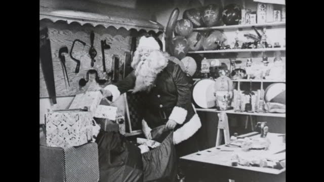 1939 santa packs workshop toys into sack - north pole stock videos & royalty-free footage