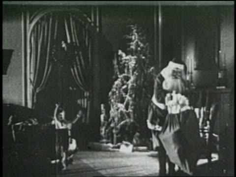 stockvideo's en b-roll-footage met b/w 1925 santa sitting down as excited children run to him + hug him - 1925