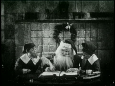 b/w 1925 santa sitting with two helpers working on christmas list - 1925 stock videos & royalty-free footage
