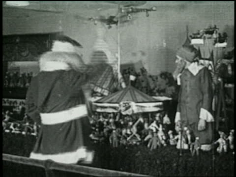 b/w 1925 santa starting toys with wave of hand in toy shop as elf looks on - 1925 stock videos & royalty-free footage