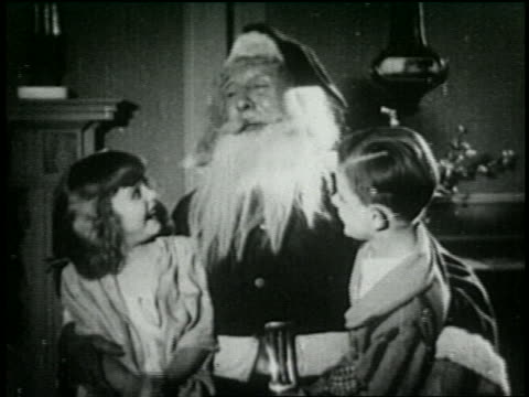 b/w 1925 santa talking to boy + girl sitting on his lap - 1925 stock videos & royalty-free footage