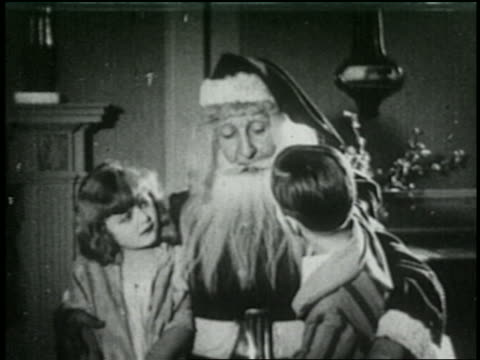 b/w 1925 santa talking to two children sitting on his lap - 1925 stock videos & royalty-free footage