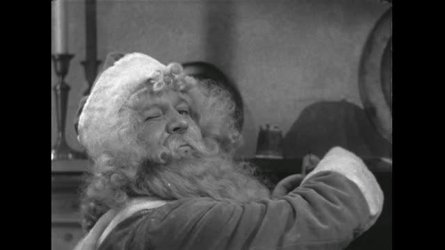 stockvideo's en b-roll-footage met 1946 santa winks and nods and fills stockings with toys - knipogen activiteit