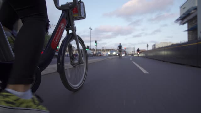 santander city bike riding near big ben and houses of parliament at dusk, london, england, united kingdom, europe - big ben点の映像素材/bロール