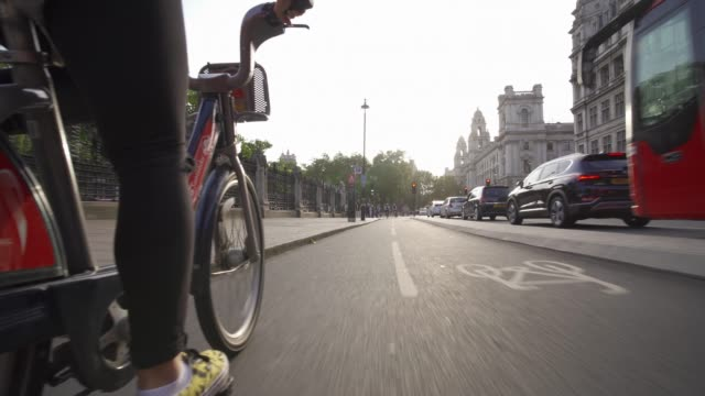 santander city bike riding near big ben and houses of parliament, london, england, united kingdom, europe - uk politics stock videos & royalty-free footage