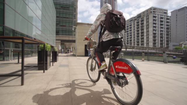 santander city bike riding through canary wharf, docklands, london, england, united kingdom, europe - cycling stock videos & royalty-free footage
