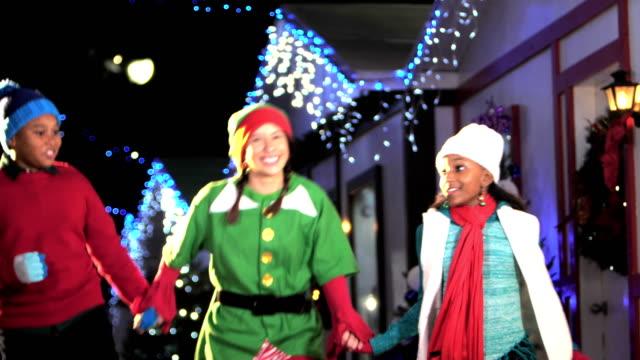 サンタのエルフの 2 人の子供が付いている村を通ってとび - エルフ点の映像素材/bロール