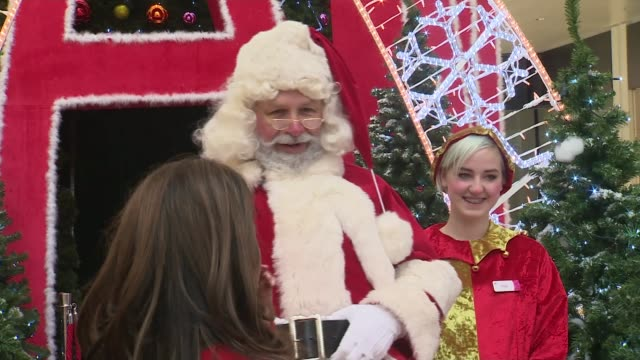 santa's grotto trained to welcome children with autism; england: west sussex: crawley: int father christmas along from grotto towards school children... - west sussex stock videos & royalty-free footage