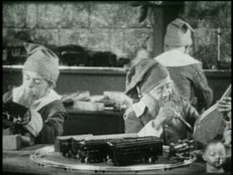b/w 1925 santa's helpers building toys in toy workshop - 1925 stock videos & royalty-free footage