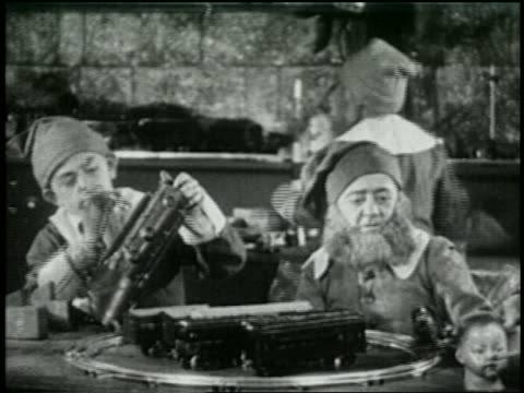 b/w 1925 santa's helpers working with electric train set in toy workshop - 1925 stock videos & royalty-free footage