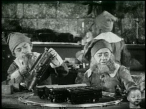 vidéos et rushes de b/w 1925 santa's helpers working with electric train set in toy workshop - 1925