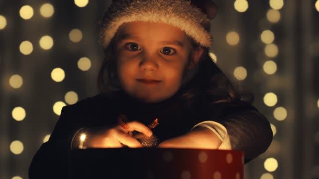 vídeos y material grabado en eventos de stock de la pequeña ayudante de papá noel jugando con su regalo de navidad - regalo de navidad