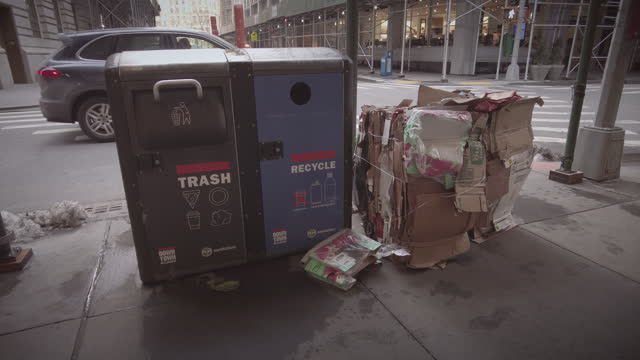 vídeos de stock, filmes e b-roll de santation - garbage recycling bins and cardboard recycling next to it on the sidewalk in lower manhattan. people are walking by wearing protective... - saco de lixo