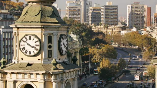 Santiago traffic passes beneath the clock tower of San Francisco Church.