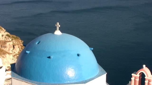 santorin, griechenland. die blauen kuppeln der kirche mit kreuz gegen die ägäis. - insel santorin stock-videos und b-roll-filmmaterial