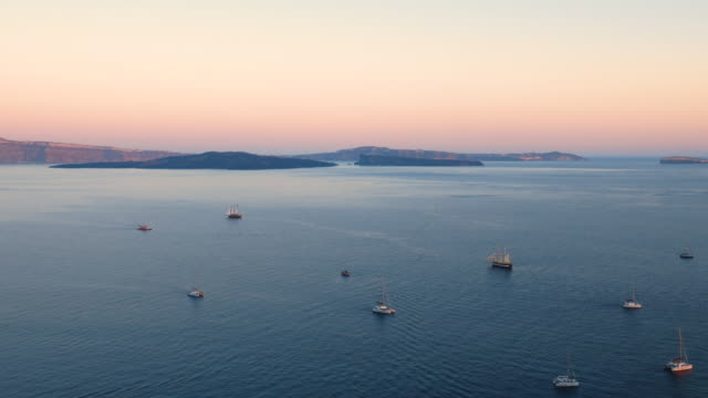santorini sunset with boats at aegean sea, greece, 4k resolution. - oia santorini stock videos & royalty-free footage