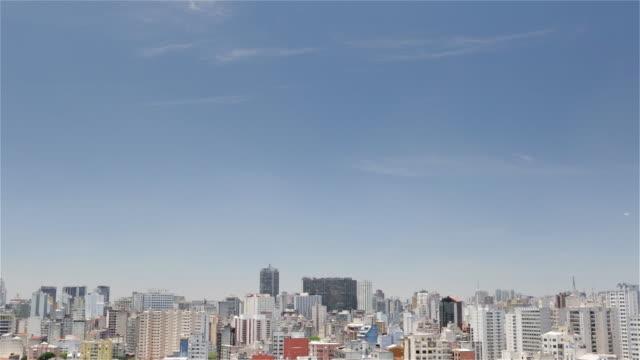 ws, ha sao paulo downtown skyline with a plane flying overhead / sao paulo, brazil - ワイドショット点の映像素材/bロール
