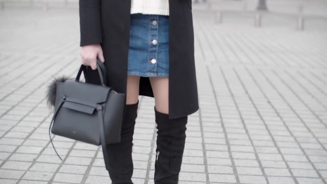 Sara Carnicella fashion blogger from La Fille Rebelle wears a Zara black coat a Zara white pull over Zara black thigh high boots an HM blue denim...