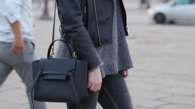 sara carnicella, fashion blogger, wears sol amor sunglasses, a zara black leather jacket, a bag, a zara wool gray pull over, zara black denim jeans,... - gray jacket stock videos & royalty-free footage