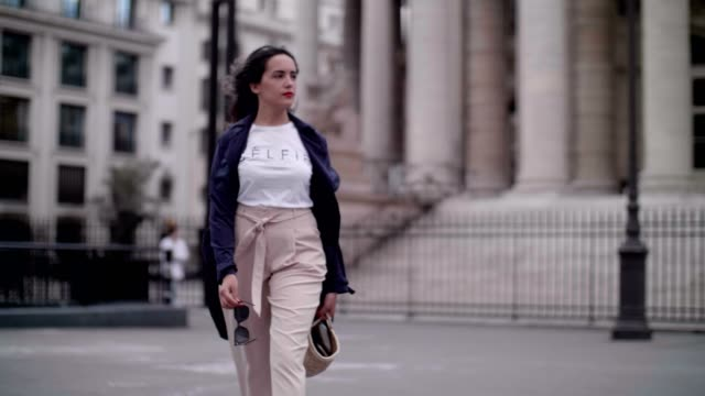 sarah benziane fashion blogger wears a new look blue trench coat a white tshirt with the inscription 'celfie' new look cropped pants a straw basket... - pink shirt stock videos and b-roll footage