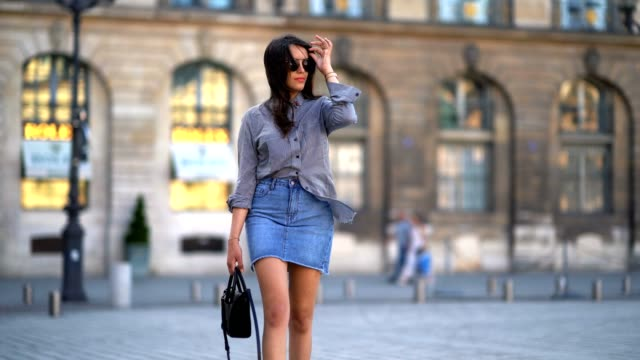 Sarah Benziane fashion blogger wears a The Kooples gingham shirt a New Look blue denim skirt an Ali Express bag sunglasses and Zara white shoes at...