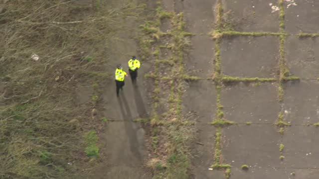 air views of police searches in ashford, dover and deal; england: kent: dover: ext air views / aerials police vehicles and police officers at site of... - run down stock videos & royalty-free footage