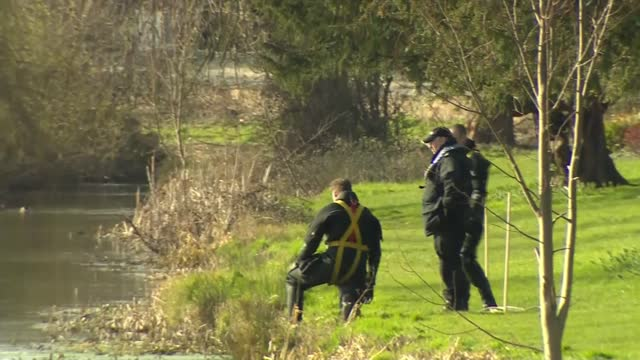 police searching in sandwich in kent; england: kent: sandwich: ext police officer wading into river and taking item from search and rescue diver in... - walking in water stock videos & royalty-free footage