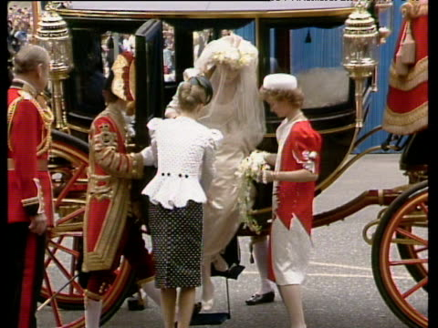 Sarah Ferguson is helped from carriage her wedding dress and veil are arranged by woman in black and white outfit Westminster Abbey Royal Wedding of...