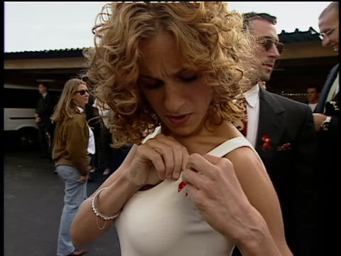 Sarah Jessica Parker is putting on her red AIDS support ribbon outside of 1993 Movie Awards
