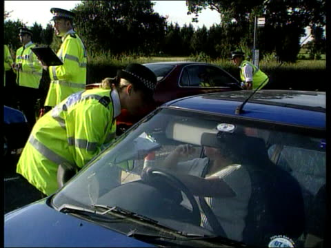 police checkpoints a2300 BEN MCCARTHY ENGLAND West Sussex Pulborough Police officer flagging down car to question driver at checkpoint near place...